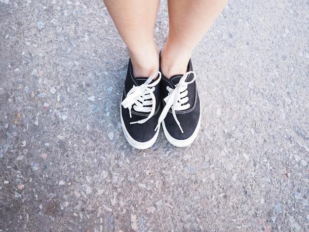Закройте ноги азиатской девушки с черными кроссовками, стоящими на бетонной дороге. хипстерский образ жизни.