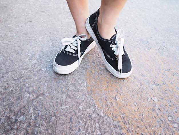 コンクリートの道に立っている黒いスニーカーでアジアの女の子の足を閉じます。流行に敏感なライフスタイル。