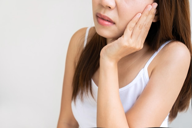 白い背景の上の強い歯痛に苦しんでいる手で頬に触れるアジアの女の子をクローズアップ