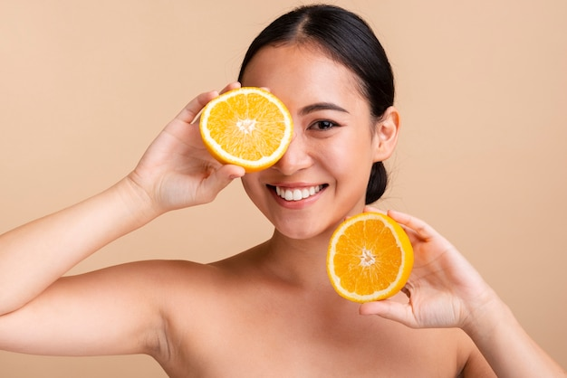 Азиатская девушка крупным планом с апельсином