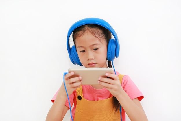 흰색 배경에 격리된 스마트폰에서 헤드폰을 끼고 재미있는 게임을 하는 클로즈업 아시아 소녀