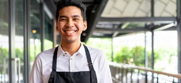 Close up asian man barista smiling outside of coffee cafe shop background , sme business concept