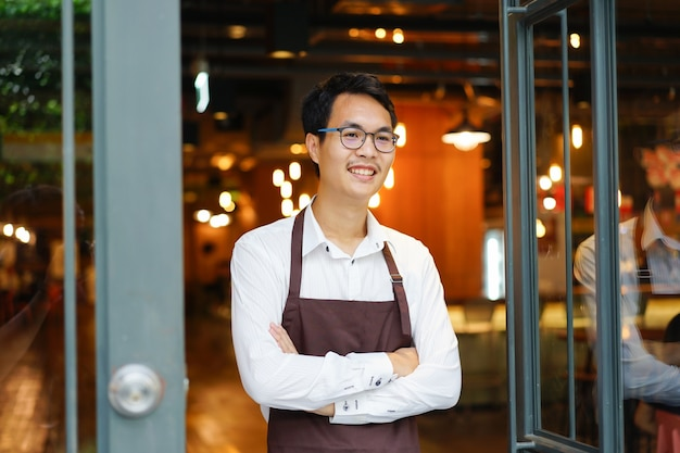 Close up asian man barista standing at coffee cafe shop background