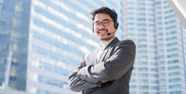 クローズアップアジア人男性コールセンターエージェントはヘッドセットデバイスを着用し、将来のテレマーケティングとヘルプデスクの概念のために都市の建物の背景をぼかすために外のオフィスで微笑む