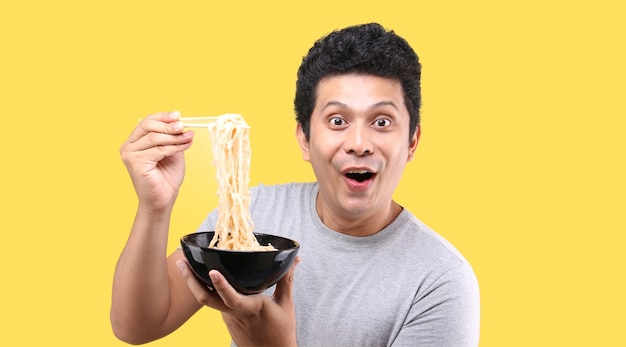 Close up of asian man eating yummy hot and spicy instant noodle using chopsticks and bowl