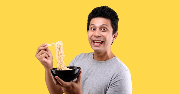 Close up asian man eating yummy hot and spicy instant noodle using chopsticks and bowl