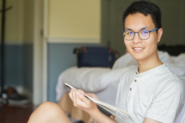 Close up asian man reading book in bedroom