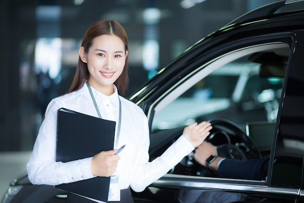 Close up on asian saleswoman in auto car sale