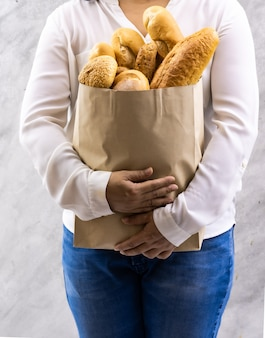 Close up of asian smile woman housewife holding variety bread in disposable paper bag on grey vintage loft background. bakery food and drink grocery and domestic life lifestyle concept for delivery.