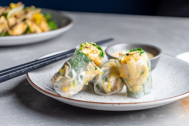 豆腐とアジアの春巻きを閉じます。汎アジア料理。コピースペースとストリートフードのコンセプト。灰色の背景。ランチやスナックのための平らな食品。ビーガンで健康的でバランスのとれた食事。動物肉の概念はありません