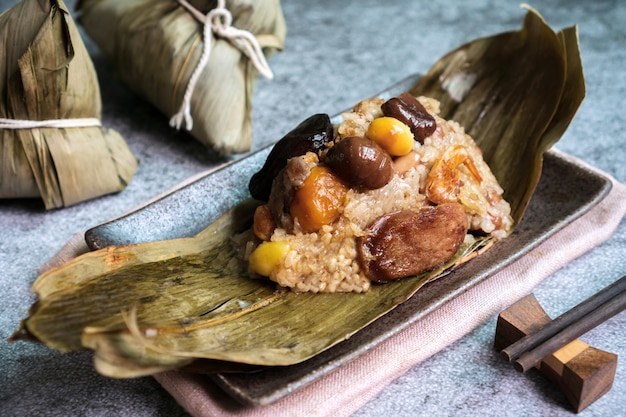 Close up of asian tasty home made food in dragon boat (duan wu) festival, rice dumplings or zongzi wrapped by dried bamboo leaves on plate with tea on black surface