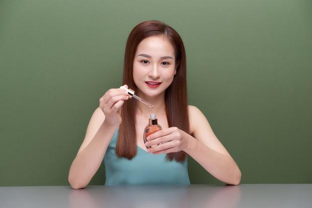 完璧な肌でアジアの女性20代をクローズアップ、ヌードメイクは緑の壁の背景に分離された顔にボトルからオイルを適用します