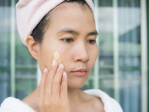 아시아 여자를 닫습니다 자외선 차단을 위해 얼굴에 자외선 차단제를 바르십시오. 주근깨, 검은 반점의 원인. 황갈색 피부. 아름다움 개념.