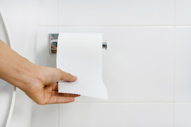 Close up of asian woman hand  pulling paper in bathroom
