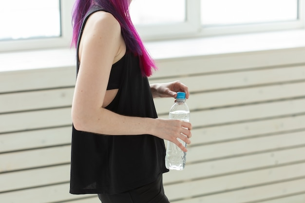 Close up of asian woman holding water after gym workout