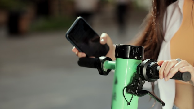 クローズアップアジアの女性が携帯電話アプリを使用して電動スクーターを借りる都市のエコ輸送で開始された新しい共有ビジネスプロジェクト