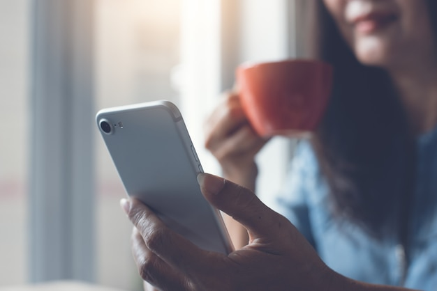 Close up of asian woman using mobile phone and drinking coffee