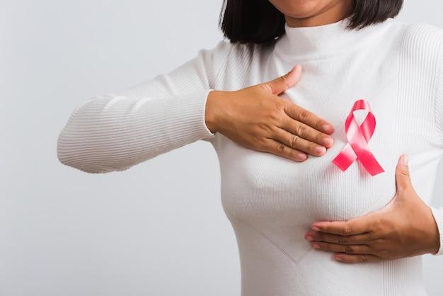 クローズアップアジアの女性は彼女が手で胸を保持している胸にピンクの乳がん啓発リボンを持っているtシャツを着ています