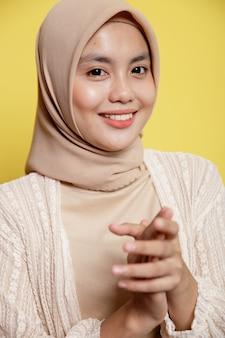 黄色の壁に分離された笑顔のヒジャーブを握りしめる手を身に着けているアジアの女性をクローズアップ