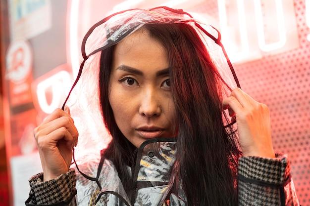 レインコートを着ているクローズアップアジアの女性