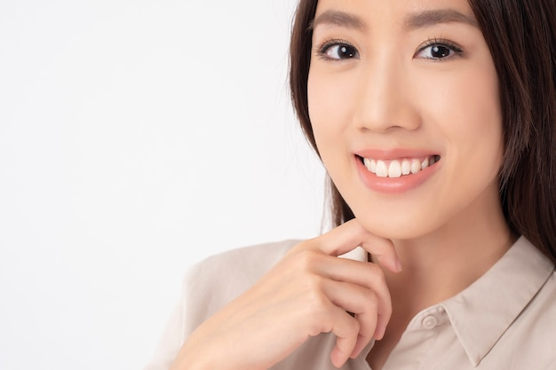 Close up of asian woman with beautiful teeth on white wall