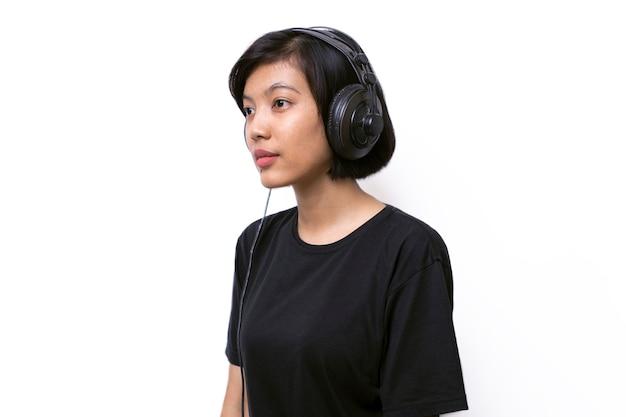 Крупным планом азиатская женщина с наушниками, наслаждаясь музыкой на белом пространстве