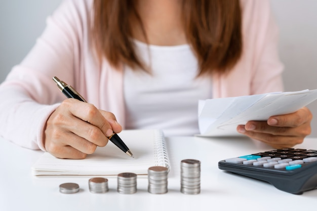 Close up of asian woman writing monthy cost summary on notebook while holding receipt with calculator