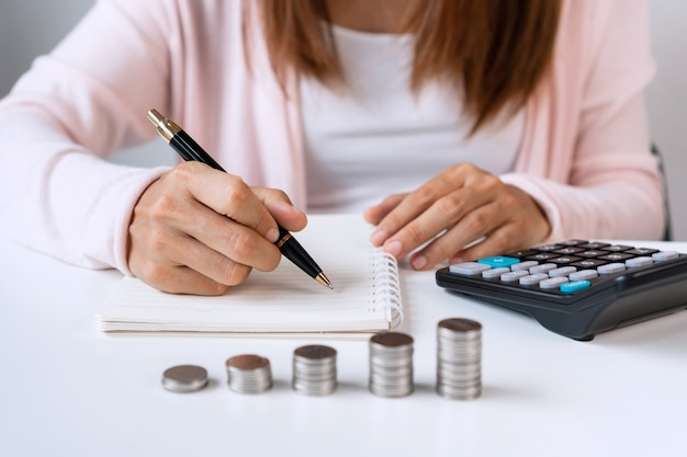 Close up of asian woman writing on notebook with calculator and coins pile on white table