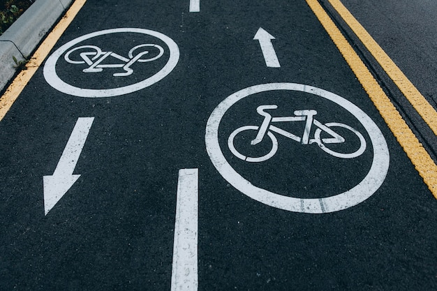 Close up of asphalt road for cyclists in two directions. white circle with sign bike in the middle and arrow in front. way for transport.