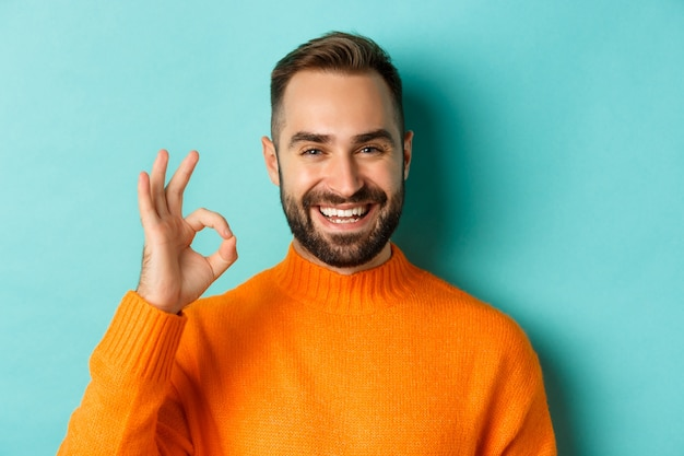 Close-up of assertive young man assuring everything ok, showing okay sign and smiling, yes or positive answer, standing over light blue background.