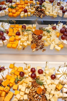 Close up of assorted cheeses with nuts and grapes.