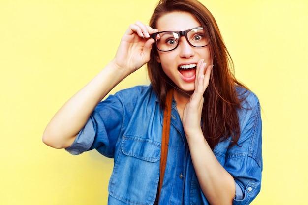 Primo piano della ragazza stupita che tocca i suoi occhiali
