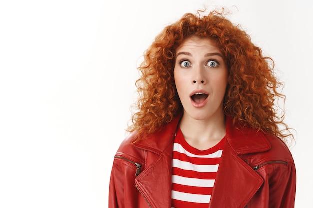 クローズアップ驚いた驚いた興奮した赤毛の縮れ毛の女の子青い目がスタイリッシュでモダンな赤いジャケットを着ているドロップジョーは目を広げて驚いた反応興奮素晴らしいニュース白い壁