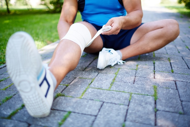 Close-up of athlete bandaging his knee