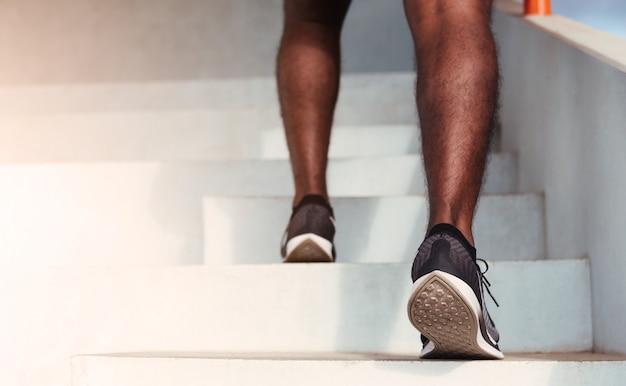 屋外でトレーニングカーディオスポーツトレーニングをしている階段を上るまで走っている足のランナーの男のステップのアスリートシューズを閉じます