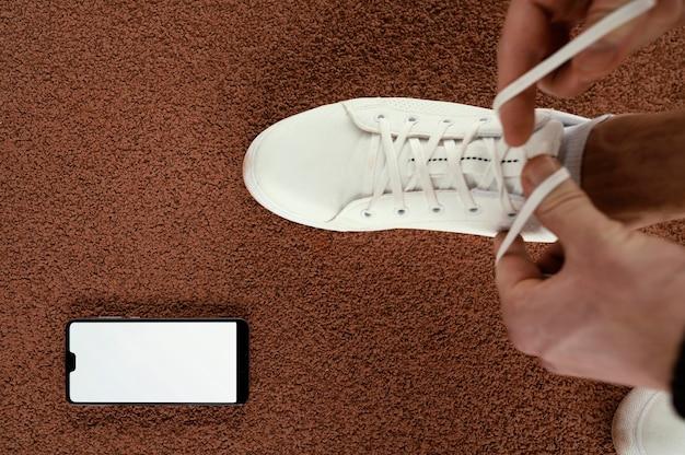 Atleta del primo piano che lega i lacci delle scarpe