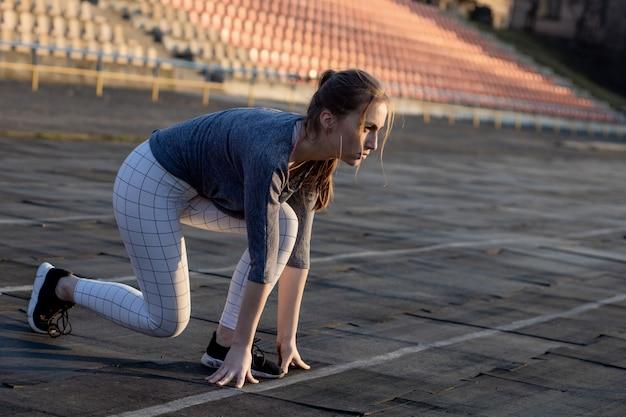 Закройте вверх спортсмена во время подготовки к бегу на беговой дорожке, начиная на стадионе