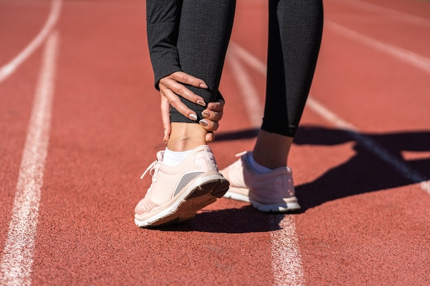 Close up of athletic woman runner touching foot in pain due to sprained ankle