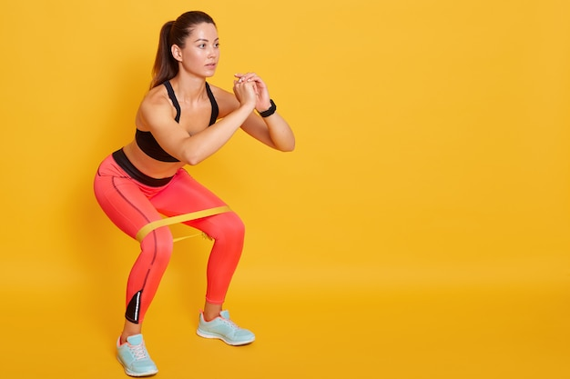 Close up of athletic woman in squat in gym, fit girl exercising with resistance band for lower body relief, sporty lady wearing sport clothes and sneakers posing isolated over yellow studio wall