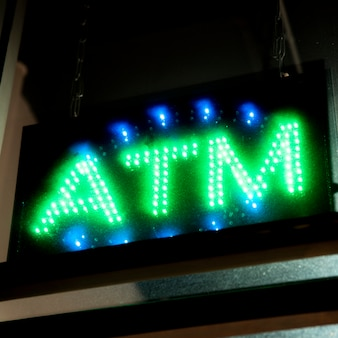 Close-up atm sign in neon lights