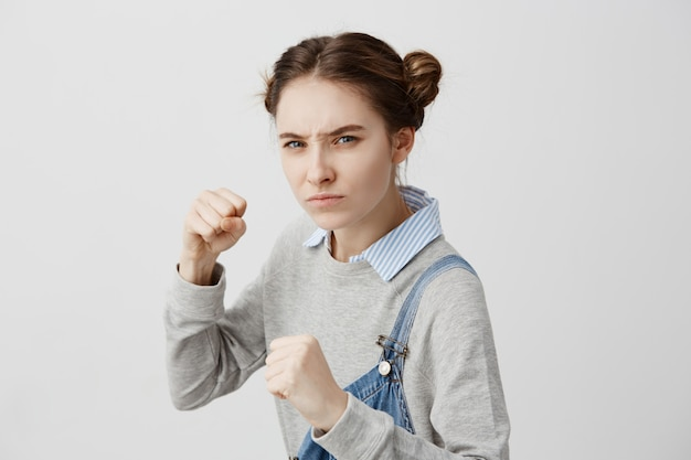 犯人を見て戦う準備ができていると確信している女性の攻撃位置を閉じます。スポーツクラブで筋力トレーニングでパンチしようと渋面の女子高生。行動、スポーツ