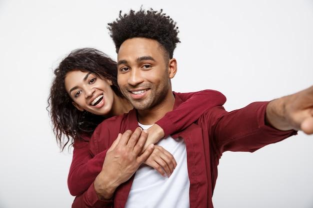 かわいいジェスチャーでセルフを作る魅力的なアフリカ系アメリカ人のカップルを閉じます。