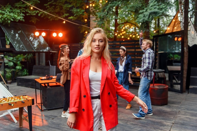 Close up of attractive blond girl with blue eyes posing to the camera with her friends dancing in disco light on the background. outdoors evening party concept.