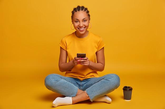 Primo piano su attraente spensierata giovane donna seduta sul pavimento