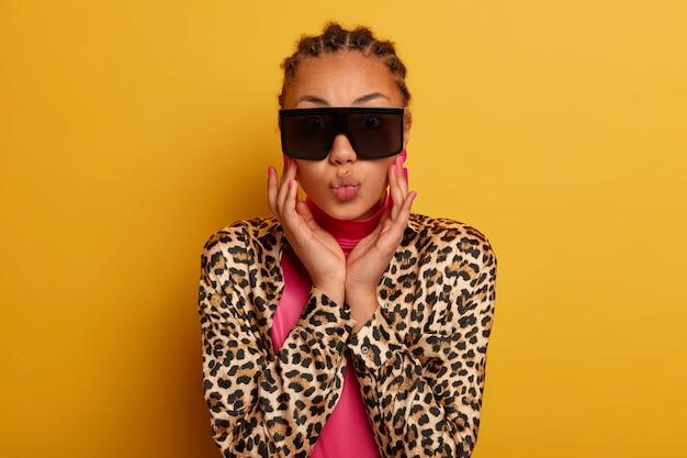 Primo piano su attraente spensierata giovane donna che indossa occhiali da sole
