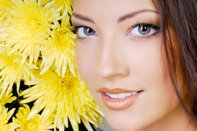 Крупным планом привлекательное женское лицо с желтой ромашкой