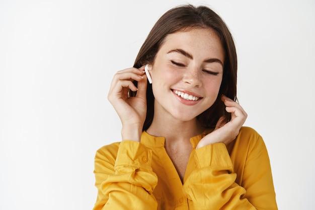 Primo piano di una donna attraente che ascolta musica in cuffia, sorride mentre si gode una canzone agghiacciante, in piedi su un muro bianco