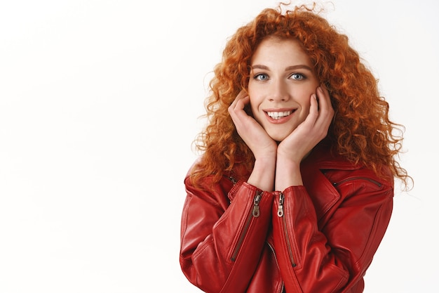 クローズアップ魅力的な生姜の女の子巻き毛の髪型青い目愚かな笑顔素敵な興奮した完璧な最初のデート立っている陽気なタッチ頬赤面話す愚かなロマンチックなもの、白い壁