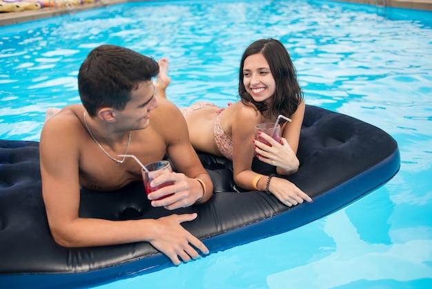 Макро привлекательный парень и улыбающаяся девушка лежит на матрасе в бассейне с коктейлями
