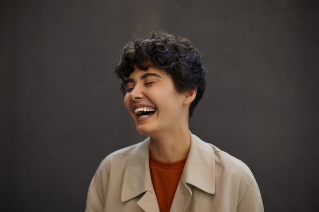 Close-up di attraente felice giovane donna dai capelli scuri con taglio di capelli corto ridendo felicemente con gli occhi chiusi, essendo in alto spirito mentre si cammina fuori, indossando abiti alla moda